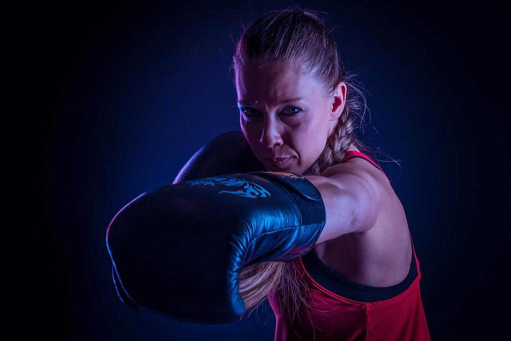 Kick box portretfoto van een stoere, sportieve vrouw met kick box handschoenen aan. Deze foto is gemaakt tijdens een sport fotoshoot waarbij zij haar beste moves laat zien.