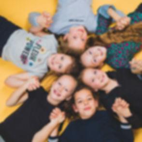 Deze portretfoto is van bovenaf gemaakt op een gele achtergrond. Tijdens een fotoshoot van een kinderfeestje zullen we meerdere foto's maken van iedereen samen zodat er altijd wel een leuke foto tussen zit!  Professional photo of six girl friends.