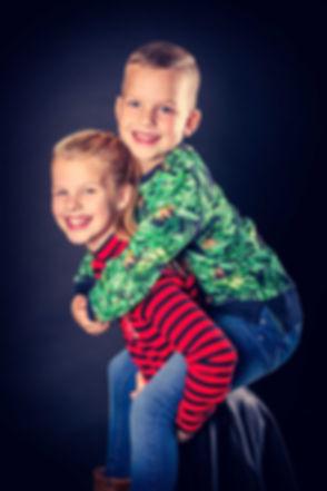 Kinderfotoshoot waarbij het broertje op de rug van zijn grote zus zit. Een portretfoto gemaakt met een zwarte achtergrond. De kinderen lachen op de foto. Wil jij een fotoshoot cadeau geven aan bijv. de kinderen van jouw zus of vriendin? Een cadeaubon kan worden opgehaald in de fotostudio. Children's photoshoot where a brother sits on he's sisters back.