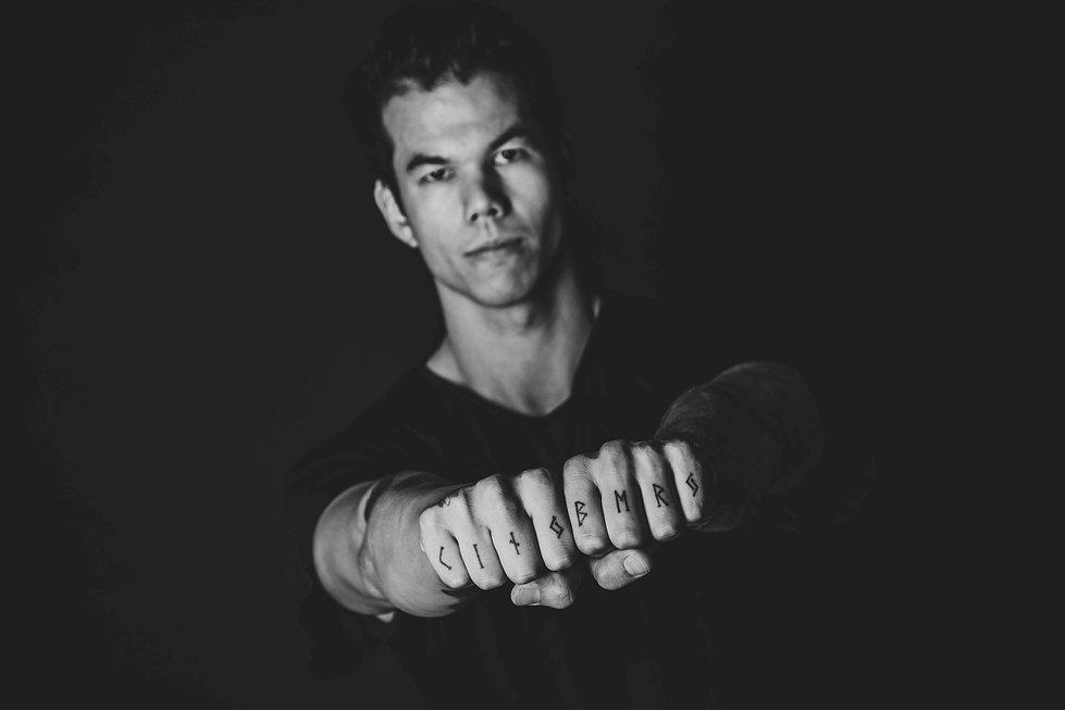 Foto van de handen van een man die tattoo's op zijn vingers heeft. Een zwart wit foto waarbij de handen scherp zijn en het gezicht van deze man wazig is. Professionele tattoo fotografie in Nederland. Professional tattoo photography in Holland. Black and white photo of tattooed hands.