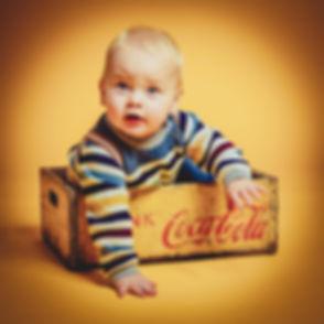 De fotoshoot van deze peuter was ontzettend gaaf om te doen omdat hij zo aan het lachen was. Hij zit in een vintage coca cola kratje op een gelige achtergrond wat de foto lekker retro maakt.  Toddler sits in a vintage coca cola crate.