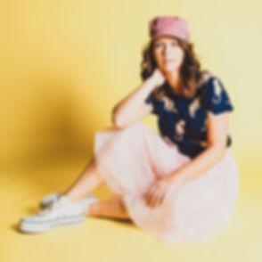 Een vrolijke, kleurrijke portretfoto waarbij er gebruik gemaakt is van een gele achtergrond. Boek nu ook jouw fotoshoot bij dé fotostudio in Nederland.