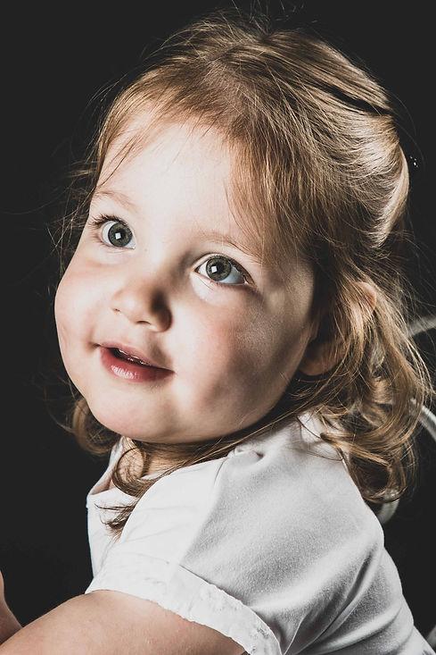 Deze kleine meid is gefotografeerd door bekende Nederlandse fotograaf Nikki Hoff tijdens een kindershoot. Op deze portretfoto kijkt de peuter weg van de camera.  Close up portrait photo of a toddler. Made in a photostudio.
