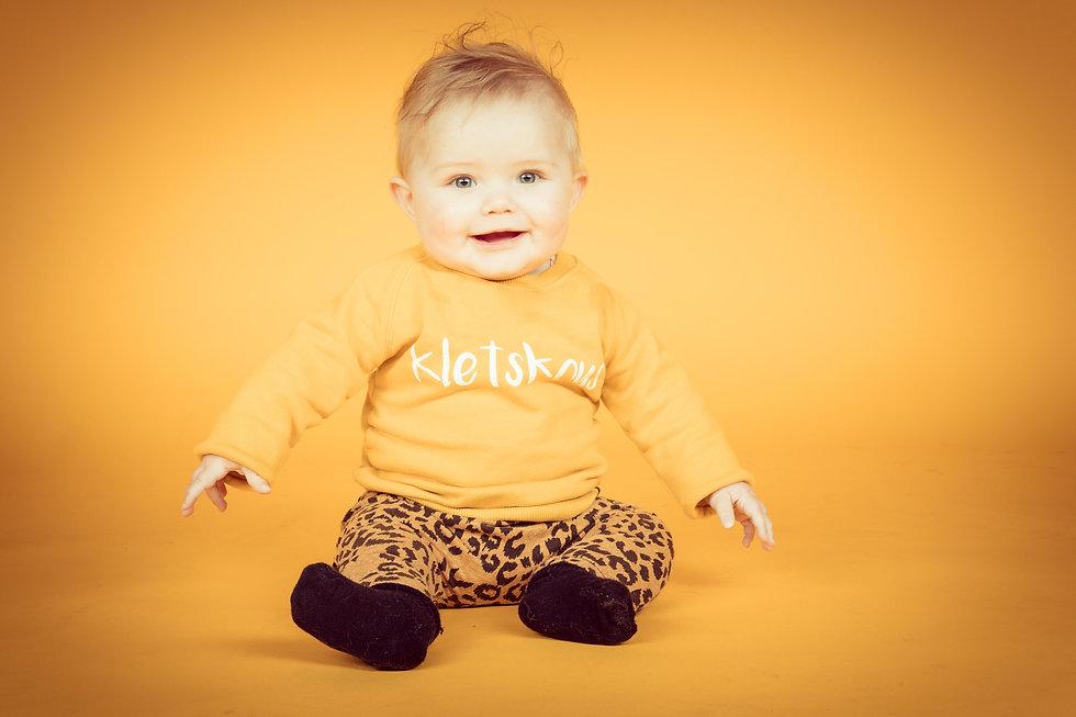 Studiofotografie waarbij deze baby op een gele achtergrond is gefotografeerd. Voor de mooiste portretfoto's van jouw kinderen kan je terecht bij fotostudio Studio86 te Alphen aan den Rijn.  Cute little baby girl sitting on a yellow background. Baby photoshoot.