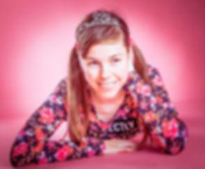 De prijs van een fotoshoot voor kinderen is te vinden www.studio86.nl. Deze tiener meid was helemaal verliefd op deze roze achtergrond. Haar shirt heeft roze bloemen waardoor hij goed bij de setting past. Wil jij ook een portretfoto laten maken van jouw dochter? Nikki is een beroemde fotograaf en helpt jou hier graag bij. A teenager girl on a pink background wearing a tiara.