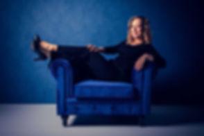 Nikki is één van de bekende Nederlandse vrouwelijke fotografen en heeft een moderne fotostudio. Hier zie je een zelfverzekerde dame op een fluweel blauwe chesterfield bank zitten wat mooi staat bij de witte vloer en blauwe muur. Ook deze portretfoto zou goed op instagram kunnen worden gebruikt.