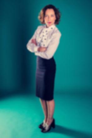 Een stoere castingfoto van Lot Bobbink gemaakt door bekende Nederlandse fotograaf Nikki Hoff. Deze actrice staat met haar armen over elkaar op een turquoise achtergrond.