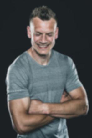 Lachende man in sportshirt. Niet alleen worden er serieuze foto's gemaakt tijdens een fitness fotoshoot, er komt ook een hoop gezelligheid bij kijken waardoor dit soort lachende foto's ontstaan.  Smiling man wearing a sport shirt. This portrait photo is made by Nikki Hoff. She has a photo studio and makes fitness photo's.