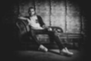 In de fotostudio zijn er diverse meubels / accessoire aanwezig om voor een gevarieerde fotoshoot te zorgen. Deze chesterfield bank doet het goed tijdens een fotoshoot van een man omdat je er diverse stoere poses op kan aanhouden.  Sexy man sitting on a couch. A black and white shit made by famous photographer Nikki Hoff.