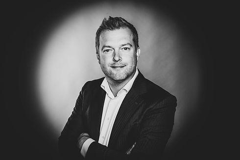 Deze zakelijke portretfoto's zijn gemaakt voor kinki kappers in Alphen aan den Rijn. Ze zijn stuk voor stuk uniek omdat er bij alle personeelsleden een ander kleur haarlicht is gebruikt.  Professional photograph of handsome man in suit.