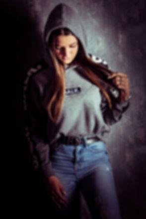 Stoere portretfoto van een jonge meid die tegen een muur aanstaat en naar beneden kijkt. Stoere en creative studiofotografie in Alphen aan den Rijn. Tough portrait of a young girl who leans against a wall in the photo studio. Creative photography in Holland.