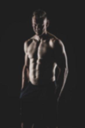 Altijd leuk als een man met blokjes lacht, omdat de spieren dan extra worden aangespannen en deze dus nog meer zichtbaar zijn op de foto. Deze portretfoto is gemaakt tijdens een fitness shoot met een zwarte achtergrond.  Smiling sexy muscled man. Fitness photography in the photo studio in Alphen aan den Rijn.
