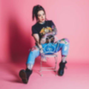 Hier zit Miss Vief op een kinderstoeltje op een roze achtergrond, wat een ontzettend tof contrast is bij haar tatoeages. Miss Vief is bekend als vlogger en influencer en zal binnenkort ook haar eigen programma hebben. Een studiofoto gemaakt door studiofotograaf Nikki. Studio portrait made by famous photographer Nikki.