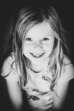 Kinderfotografie door fotograaf Nikki Hoff in Alphen aan den Rijn. Portretfotografie met een zwarte achtergrond.  Black and white photography. Close up portrait picture of a young girl.