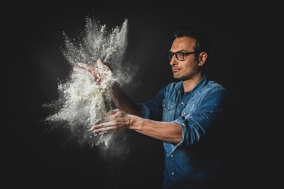 Op deze foto zie je de bloem of het meel uit elkaar spatten wat een ontzettend tof effect geeft. Deze ondernemer heeft zijn eigen pizza tuk tuk en heeft een fotoreportage laten maken voor zijn website.  Italian man who is an Italian chef playing with flower. Cool food photography for website.