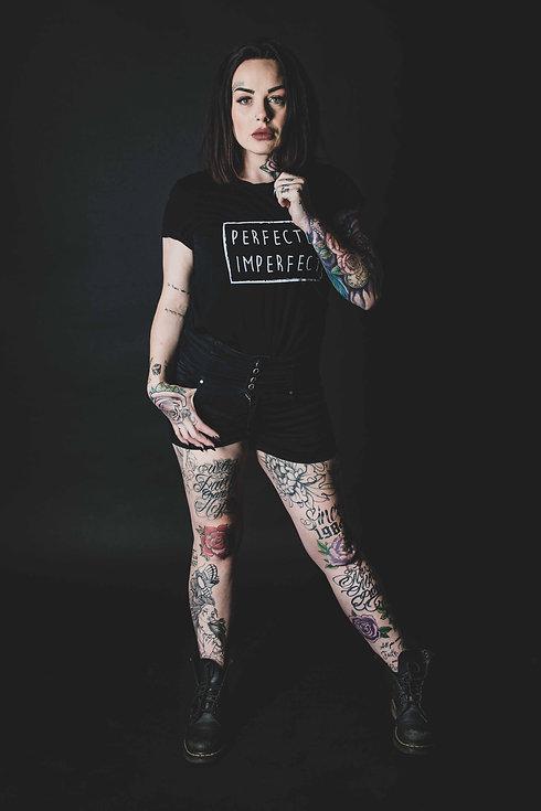Wil jij een sexy portretfoto laten maken waarop jouw tattoo's goed zichtbaar zijn? Hier zie je een sexy dame met een korte broek en een zwart shirt waarop; perfectly imperfect op staat, wat perfect bij haar getatoeëerde lichaam past. Door de zwarte achtergrond komen haar gekleurde tattoo's goed uit. Sexy portrait photo of a lady with colorful tatoos. Professional studio photography.