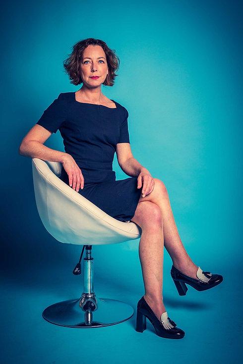 Actrice Lot Bobbink zit hier in een mooi, strak, blauw jurkje op een witte stoel. Door de felle blauwe achtergrond knalt deze castingfoto eruit! Bekende Nederlandse fotograaf Nikki Hoff maakt graag jouw castingfoto's.