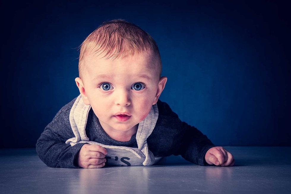 Deze babyfoto is gemaakt in de moderne fotostudio van goede fotografe Nikki Hoff. Zij is de eigenaresse van fotostudio Studio86 in Alphen a/d Rijn. De blauwe ogen van deze baby komen extra goed uit op de blauwe achtergrond. Dus ga jij een fotograaf zoeken voor jouw baby? Dan is deze goede fotografe zeker een aanrader!