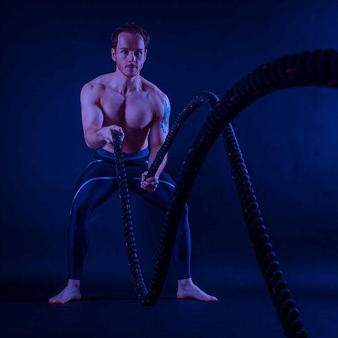 Een sportieve foto gemaakt in de fotostudio van een man die aan het sporten is met een battle rope. Nikki is een fitness fotograaf en heeft verschillende sport accessoires in de studio zoals deze battle rope. Een creatieve fitnessfoto. Creative fitness photo of a man with a battle rope.