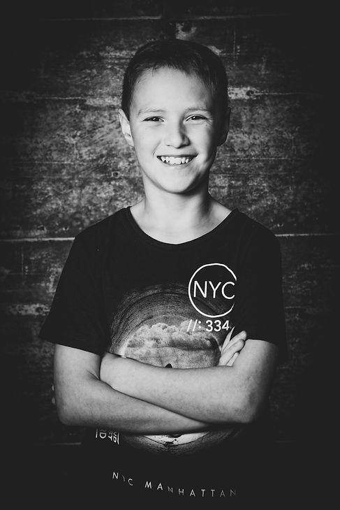 Tijdens de familie- of gezinsfotoshoot worden er ook van iedereen apart mooie portretfoto's gemaakt. Zo krijg je een ontzettend leuke en afwisselende fotoshoot.  Black and white profile photo of a young boy.