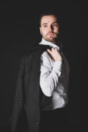 Sexy jongeman in pak is gefotografeerd door beroemde fotografe Nikki Hoff tegen een zwarte achtergrond. Deze foto kan gebruikt worden voor in bijv. een portfolio voor als je model wilt worden.  Sexy young man in suit is photographed by famous photographer Nikki Hoff against a black background. This photo can be used for a portfolio if u wanna be a model.