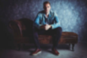 Voor een gevarieerde, unieke en persoonlijke fotoshoot ben je bij fotografe Nikki Hoff aan het goede adres. Met haar ruime studio die vele achtergronden heeft, is er voor ieder wat wils!  Guy sits on a couch in the photostudio.