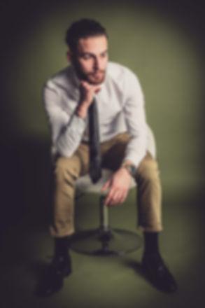 Portretfoto van man met stropdas die in een stoel zit. Deze foto kan ook tijdens een zakelijke fotoshoot gemaakt worden.  Sexy young man sits on a chair. Cool photograph made by famous photographer Nikki of Studio86. The best photostudio in the Netherlands.