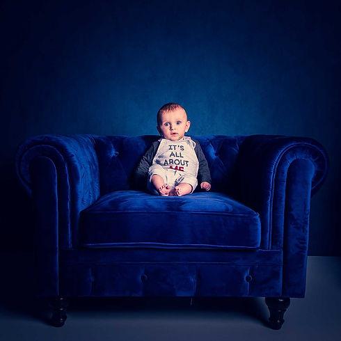 Een baby van 5 maanden zit op een fluweel blauwe Chesterfield fauteuil. Deze baby is gefotografeerd door bekende kinderfotograaf Nikki Hoff. Voor kinderfotografie in Zuid Holland is Nikki de aangewezen persoon hiervoor. Je kunt een fotoshoot ook op zondag boeken.