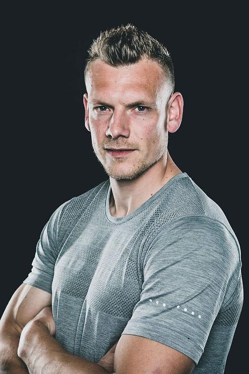 Deze knappe man is gefotografeerd in zijn sportkleding tijdens een fitnessfotoshoot.   Head shot of handsome man wearing he's sport shirt. Portrait photography.