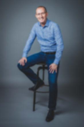 Dit is een zakelijk portret van een vrouw gemaakt door een fotografe in regio Zuid Holland. Deze portretfoto kan gebruikt worden voor linkedin en andere social media.  Business man on a high stool on a grey background. Business profile photo for linkedin, website and other social media.
