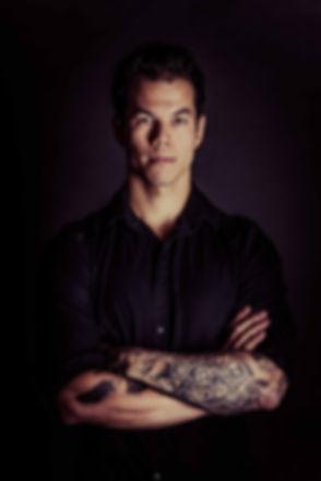 Tattoo foto van een jonge, aantrekkelijke man die met zijn armen over elkaar staat en recht in de camera kijkt. Tijdens een tattoo fotoshoot worden jouw tattoo's op een toffe manier vastgelegd. Tattoo photo of a young, handsome man who has he's arms crossed. During this photoshoot we make cool photo's of your tattoo's.