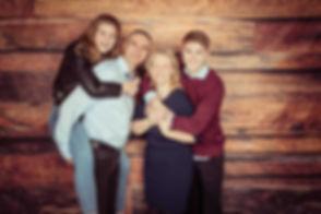 Wil jij een fotoshoot met digitale foto's boeken met het hele gezin? Nikki staat bekend als een goede familie fotograaf en heeft diverse settings in haar fotostudio om een gevarieerde familie reportage te maken. Hier staat het gezin voor de houten wand en de kinderen zitten op de rug van hun ouders.