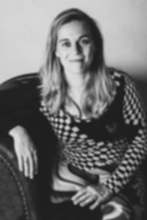 Zwart wit foto van een jonge dame die op een bank zit. Er zit schaduw in de professionele profielfoto waardoor er een stoerdere uitstraling ontstaat. Wil jij ook een profielfoto laten maken? Deze professionele fotografe is gespecialiseerd in zakelijke portretfotografie. Black and white photo of a young lody.
