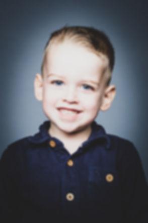 Deze stoere foto van deze peuter is gemaakt tijdens een kinder fotoshoot. Vrolijke kinderfotografie in Alphen aan den Rijn.  Close up portrait photo of a boy. Made during a children's photoshoot.