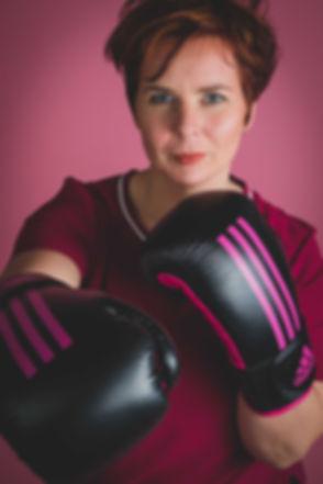 Stoere dame met bokshandschoenen aan. Deze portretfoto is gemaakt tegen een roze achtergrond in de fotostudio.  Tough young lady with box gloves. Made in a photo studio.