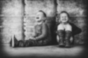 Spontane foto van kinderen kan je laten maken van bekende fotograaf Nikki Hoff in Alphen aan den Rijn.  Spontaneous photograph of 2 little kids, brother and sister, that are laughing really hard.