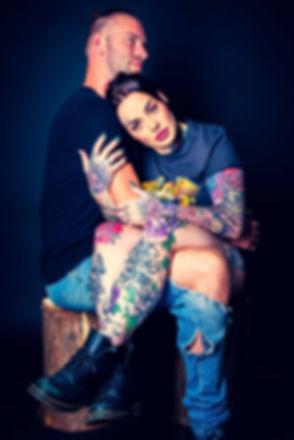 Deze pakkende portretfoto is gemaakt tijdens een tattoo fotoshoot. Hier gebruikt Miss Vief haar vriend als prop. Door de zwarte achtergrond komen haar tatoeages ontzettend goed tot hun recht. Deze prachtige portretfoto is gemaakt door bekende Nederlandse fotograaf Nikki Hoff. Colorful tattoo picture made in the photo studio of a famous photographer.