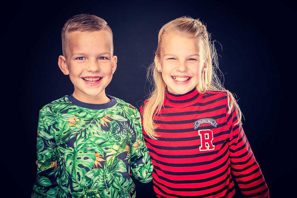 Kinderfotografie in de fotostudio. Dit is een broer en zus foto gemaakt door een kinderfotograaf. De jongen heeft een jungle trui aan en het meisje heeft een rood gestreept truitje aan. Een professionele kinderfotoshoot boek je bij Studio86. Kids photography in a photo studio.
