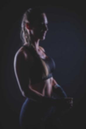 Deze fitgirl zit op kickboksen en doet op deze foto net haar bandage af. Door de zwarte achtergrond en het gebruik van het licht, worden haar buikspieren goed zichtbaar op de foto.  Sexy girl with long hair in a braid just finished her workout. She wears a top and a sport legging. She wears bandage on her hands that she wears during her kick box session.