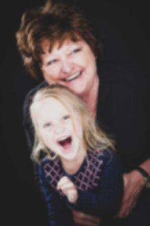 Gave portretfoto van oma en kleindochter. Gemaakt met een zwarte achtergrond en een reflectiescherm waardoor de gezichten heel mooi egaal naar voren komen. Gemaakt bij Studio86, de leukste fotostudio van Zuid Holland.  Laughing grandmother and granddaughter. Professional family photoshoot.