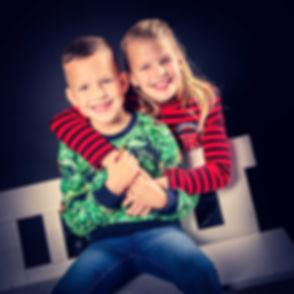 Broer en zus geven elkaar een knuffel op deze professionele portretfoto. Nikki zorgt voor een spontane fotoshoot zodat jouw kinderen een echte lach geven aan de fotograaf. Nikki is een goede kinderfotograaf in de regio Zuid Holland en heeft een inmiddels bekende fotostudio. Brother and sister hugging each other for a professional portrait photo.