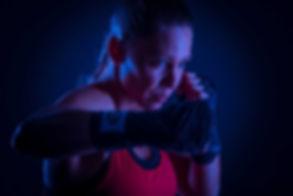 Wil jij jouw moves die je maakt tijdens het kick boksen ook eens op een stoere manier laten vastleggen? Nikki Hoff van Studio86 is sportfotograaf en maakt deze stoere foto's graag van jou tijdens een sport fotoshoot.  Kick box move by a young woman. This is photo made in a photo studio using a black background and blue light to give it an extra sporty vibe.