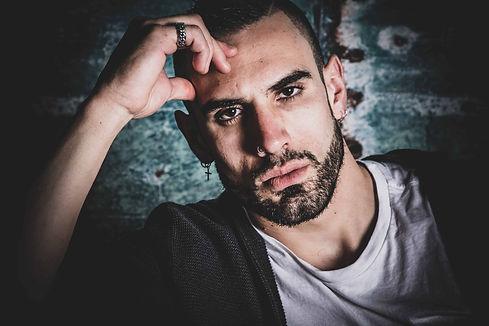 Stoere portretfoto van een Italiaanse man. Een studio foto waarbij 1 lamp is gebruikt zodat er schaduw in de foto ontstaat. Door schaduw te creëren in een portretfoto kan hij stoerder worden.  Tough portrait photo of an Italian man. A photo made in a photo studio with one flashlight, so shadow is created. A rough photo.