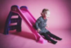 Kind op een roze glijbaan. Vrolijke foto's van kinderen.  Kid on a pink slide. happy pictures of childeren.