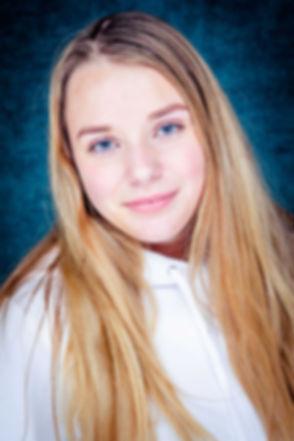 Een goede portretfoto gemaakt door een goede fotografe. Deze jonge dame heeft blauwe ogen die mooi afsteken bij de blauwe achtergrond. Ze draagt een witte sweater en heeft blond haar. Deze portretfoto is in de beste fotostudio van Nederland gemaakt, Studio86.