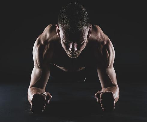 Deze man ligt in plank houding. Door dat zijn spieren zijn aangespannen en er aan beide kanten een flitslamp staat, worden deze spieren nog beter zichtbaar.  This muscled man is doing a plank. Fitness fotoshoot.