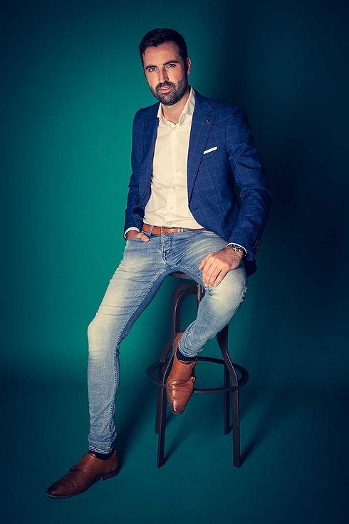Deze knappe man zit op een kruk op een turquoise achtergrond en heeft een opvallend donkerblauw jasje aan. Dit is Bjorn Remmerswaal en hij heeft een casting shoot gedaan bij de bekendste fotostudio van Nederland. Wil jij ook castingfoto's laten maken, ga dan naar www.studio86.nl Handsome man sitting on a chair on a turquoise background.