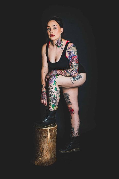 Wil jij jouw tattoo laten fotograferen op een professionele manier? Studio86 is dé fotostudio in Nederland om dit te doen! Hier zie je een dame met veel tattoo's op een zwarte achtergrond. Ze staat met 1 voet op een boomstam. Do u want a professional picture of your tattoo's? Studio is the photostudio to go to!