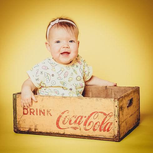Een frisse retro foto waarbij deze peuter in een vintage coca cola kratje zit op een mooie, gele achtergrond.  Toddler of one year old photographed by children's photographer Nikki Hoff. This baby girl sits in a vintage coca cola crate.