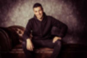 Hier zit Hamza Othman op een chesterfield bank. Deze foto is gemaakt tijdens een casting reportage. Dit is een half totaal foto.  Smiling young man sitting on a couch. Portfolio photoshoot.